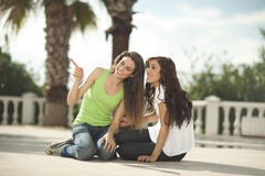 Two women having fun under palm trees Stock Photos
