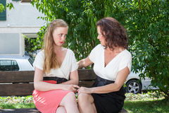 Two Women Having Heartfelt Conversation on Bench. Two Women Dressed in Formal Clothing Having Serious Heartfelt Conversation Together While Sitting on Park Bench Royalty Free Stock Photography