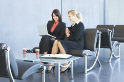 Two women having an informal business meeting, looking at a laptop Royalty Free Stock Images
