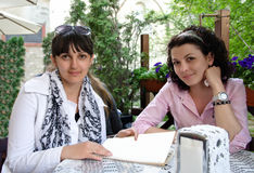Two women having a meeting outdoors. Sitting at a table on a leafy green patio discussing paperwork conceptual of a business broker, financial adviser or Royalty Free Stock Photography