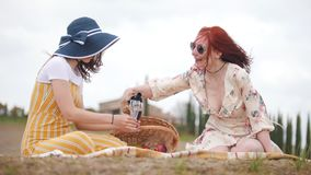 Two women having a picnic. Pouring red wine in the glasses - Tuscany stock video footage