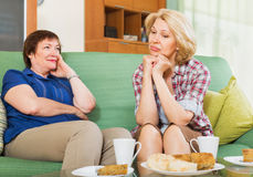 Two women having serious conversation. Two mature women friends having serious conversation at the table Royalty Free Stock Image