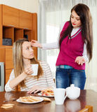 Two women having  squabble. At table in home Stock Image