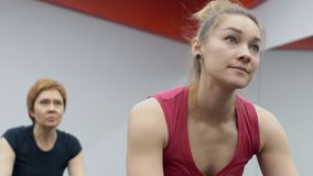 Two women are having a training on stationary bicycles in modrn gym. One lady is blond and wearing red top and her colleague is mature, with red hair and in stock video