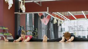 Two women are having yoga training in modern gym with mirror on the wall, slow motion. Mature female instructor in black sportswear and young blond lady are stock video footage