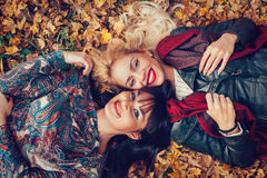 Two women head to head lying in the leaves Stock Photos
