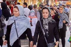 Two women in headscarves walking in crowd of citizens, Iran. Royalty Free Stock Photography