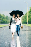 Two women in a heavy rain. Walking on a road Stock Photos