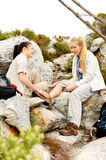Two women help each other after one of them falls. A women has sprained her ankle while hiking, her friend uses the first aid kit to tend to the injury stock image
