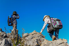 Two women hikers climbing towards the top of mountain Stock Photos