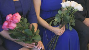 Two women hold the bouquets of roses. Two women sitting and holding bouquets of roses in the registry office stock video
