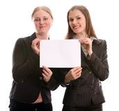 Two women holding a blank card. Isolated on white Royalty Free Stock Photography