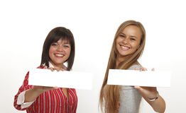 Two women is holding a blank white sign. Royalty Free Stock Images