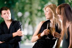 Two women holding glasses with champagne and laughing, young man. Looking at them and smiling, outdoors, focus on women Stock Photo