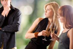 Two women holding glasses with champagne and young man looking royalty free stock photography