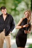 Two women holding glasses with champagne and young man looking. Two women holding glasses with champagne, young man looking at them and smiling, outdoors, focus Royalty Free Stock Photos