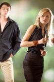 Two women holding glasses with champagne and young man looking. Two women holding glasses with champagne, young man looking at them, outdoors, focus on blond Stock Image