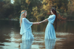 Two women holding hands. Two women holding hands, they are dressed in white dresses and are in the water stock photos