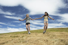 Two Women Holding Hands And Skipping Down Hill. Two women with backpacks holding hands and skipping down hill Royalty Free Stock Photos