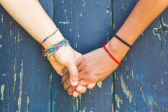 Two women holding hands. With a wooden background. One is caucasian, the other is black. Multicultural, homosexual love and friendship concepts Royalty Free Stock Images