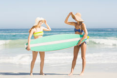 Two women holding a surfboard on the beach Stock Images
