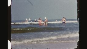 Two women holding twins and playing with waves at sea. Netherlands, Noordwijk, Summer 1956. Three shot sequence of a mother and her female friend holding two stock video footage