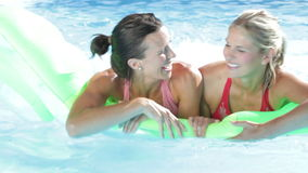 Two Women On Holiday In Swimming Pool. Two women paddle inflatable airbed across pool towards camera. Shot on Canon 5D Mk2 at at a frame rate of 25 fps stock video footage