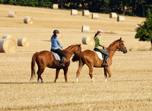 Two Women Horseback Riding in a Field Royalty Free Stock Photos