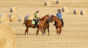 Two Women Horseback Riding in a Field Royalty Free Stock Images