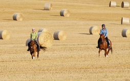Two Women Horseback Riding in a Field Stock Photos