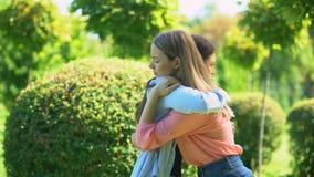 Two women hugging outdoor, saying good-bye, friendship, trusting relationship