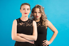 Two women in identical dresses are angry at each other Stock Images