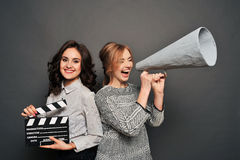 Two women inform about the beginning of shooting. With speakerphone and clapperboard Royalty Free Stock Photos