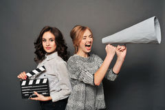 Two women inform about the beginning of shooting. With speakerphone and clapperboard Royalty Free Stock Images