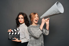 Two women inform about the beginning of shooting. With speakerphone and clapperboard Stock Images