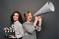 Two women inform about the beginning of shooting. With speakerphone and clapperboard Stock Photos