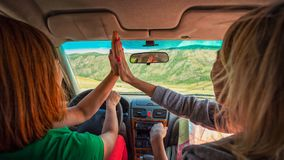 Close-up of a young tourist showing his finger. Two women inside the car driving and give five on the country roadway between fields with brown grass and snowy royalty free stock photography