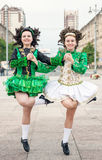 Two women in irish dance dresses and wig dancing Stock Images