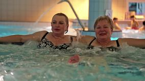 Two women in jacuzzi inside water park stock footage