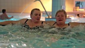 Two women in jacuzzi inside water park. Two women in jacuzzi inside big water park stock footage