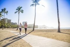Two Women jogging on the beach boardwalk between two palm trees royalty free stock photo