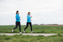 Two women jogging outdoors Royalty Free Stock Photos