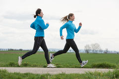 Two women jogging outdoors Royalty Free Stock Images