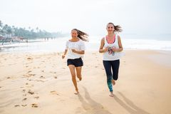 Two women is jogging the seashore on an overcast day.  Stock Photo