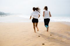 Two women is jogging the seashore on an overcast day.  Stock Images