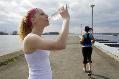 Two women jogging and taking a water break Stock Images