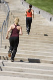 Two women jogging up steps stock photos