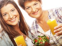 Two women with juice and salad. Happy family Royalty Free Stock Photos
