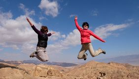 Two women jump for joy. Royalty Free Stock Image
