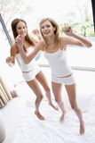 Two women jumping on bed Royalty Free Stock Photos